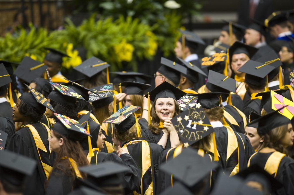 Students in graduation regalia celebrate their academic achievements at a VCU commencement ceremony
