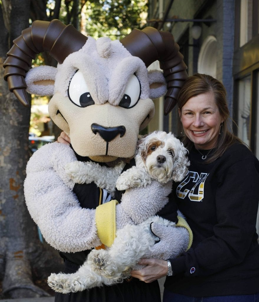 Deanna King standing next to V-C-U mascot Rodney the Ram holding a small dog.