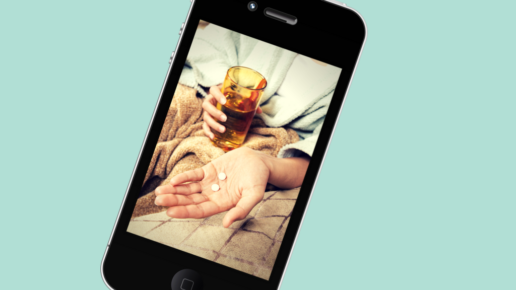 An I-phone screen shows a hand holding pills.