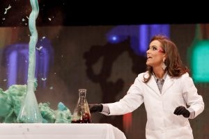 A woman in a lab coat watches a spout of green foam shooting from a flask.